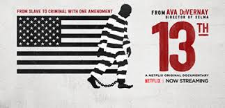 Image of U.S. flag in black and white with stripes blending into stripes on prisoner's uniform. A Black man walking with shackles on his ankles. Text: From Ava Duverney, director of Selma. 13th. A Netflix original documentary. Now streaming.